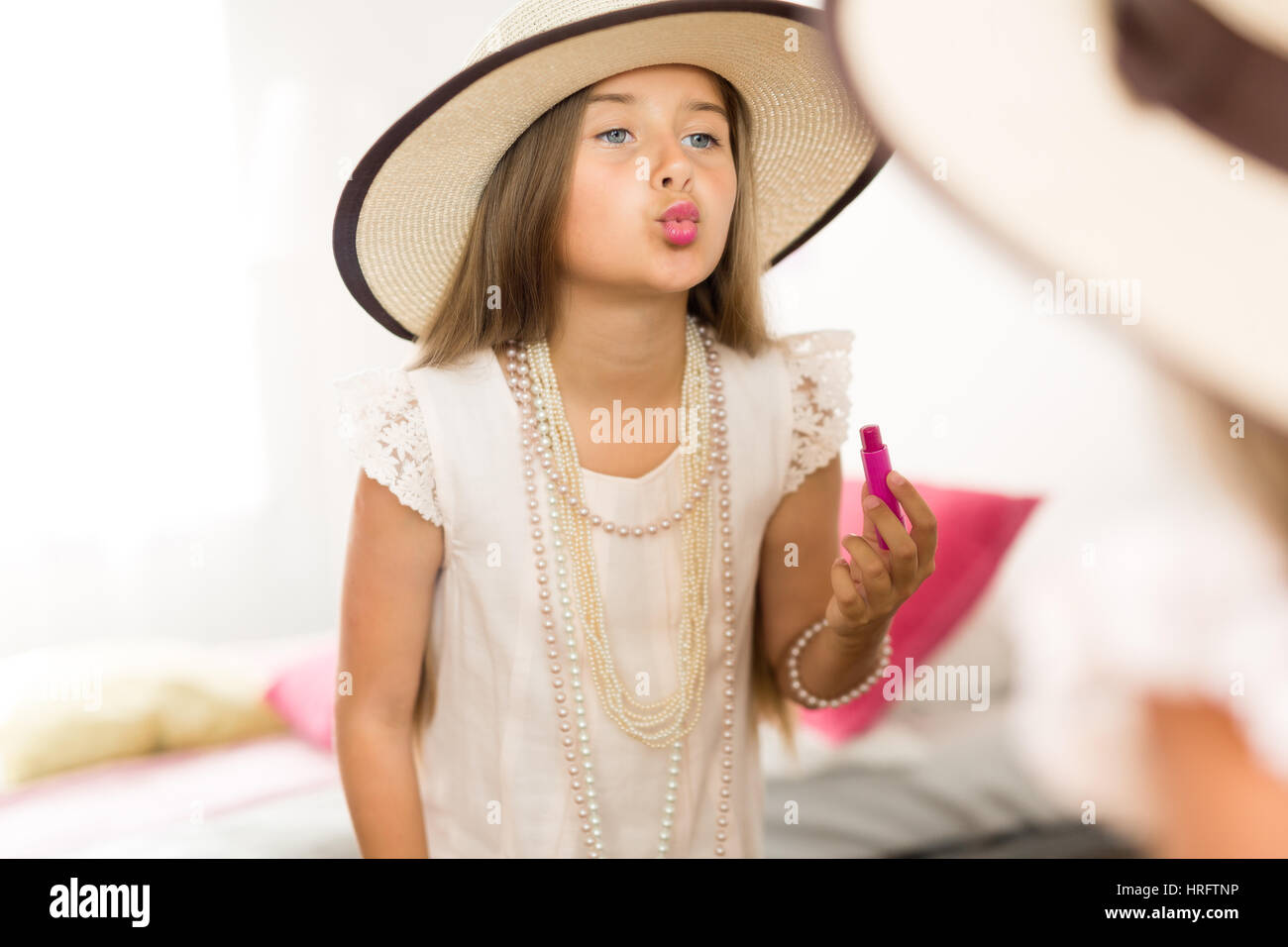 Mirror reflection shot of little girl playing dress up in mothers jewels and hat putting makeup and pink lipstick - Stock Image
