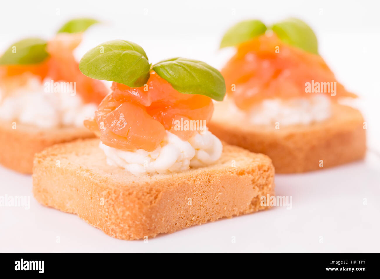 Canapes with smoked salmon, cream cheese and basil - Stock Image