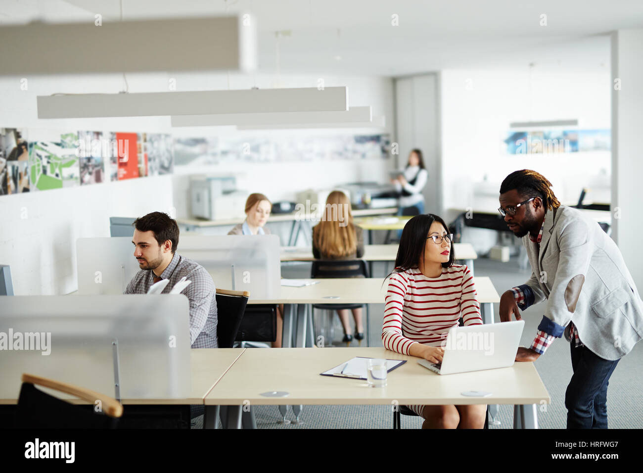 Interior of busy open plan office: male and female workers sitting at their desks, Afro-American superior discussing - Stock Image