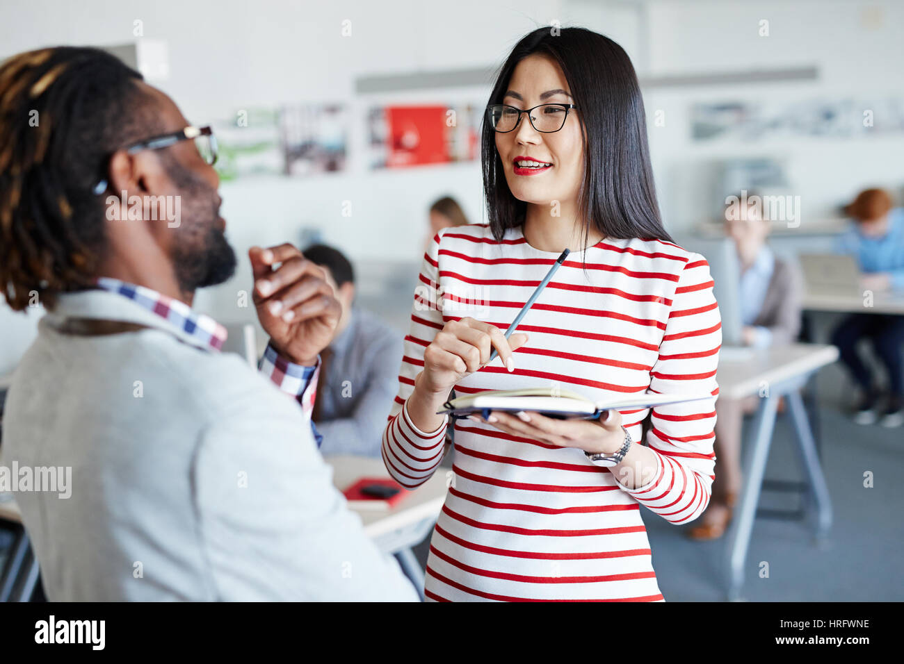 Afro-American boss with short dreadlocks giving instructions to his pretty Asian secretary, she taking notes while - Stock Image