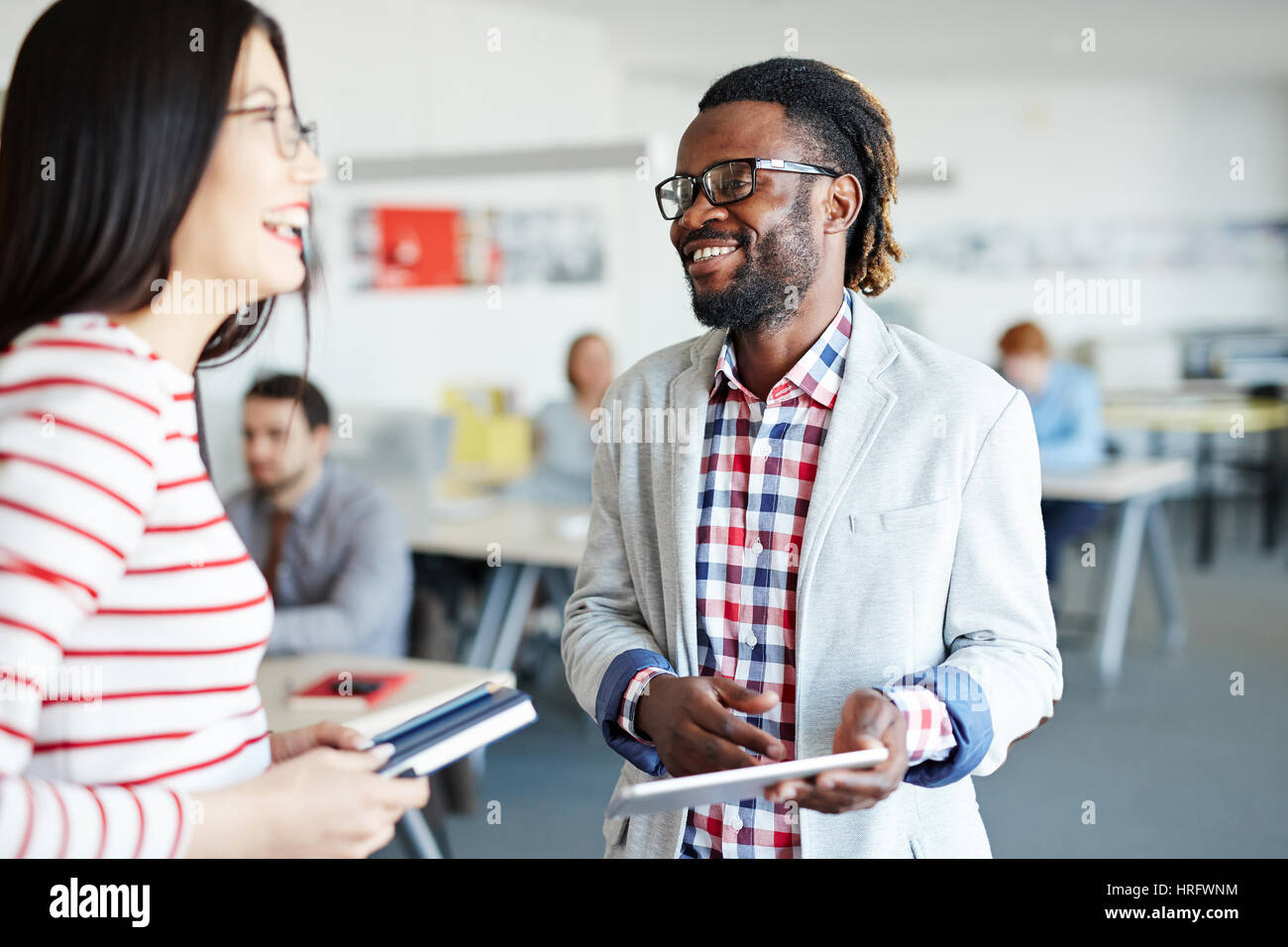 Male and female colleagues standing in open plan office and laughing at something, Afro-American employee holding - Stock Image