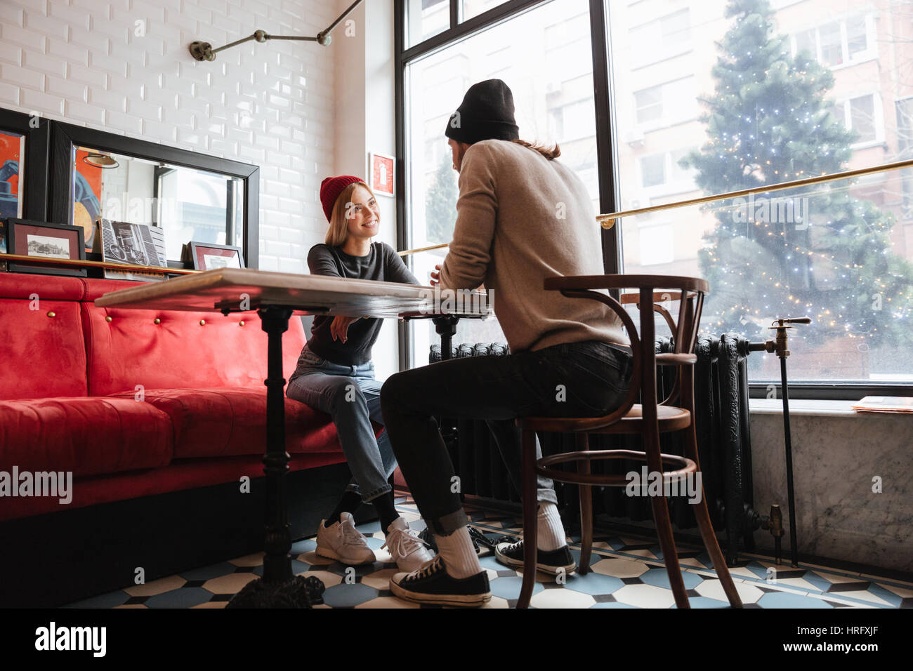 View from below of couple sitting by the table in cafe near the window - Stock Image