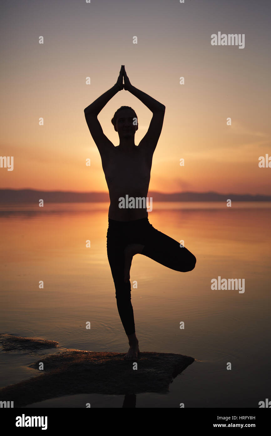 Silhouette Of Man Practicing Yoga Pose On Beach Standing One Leg And Holding Hands In Namaste