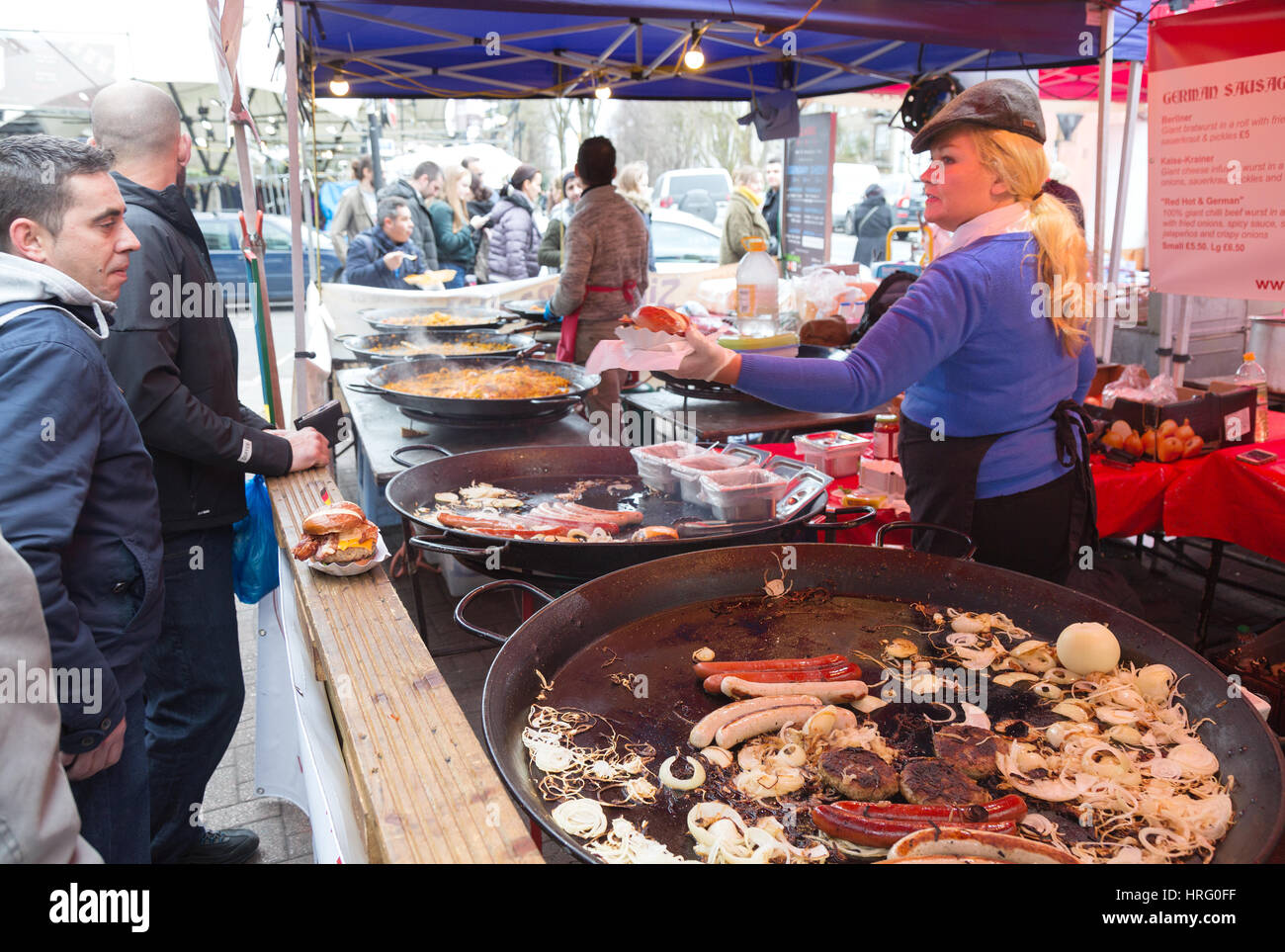 Street food London UK - People buying food at a stall, the Acklam Food Market, Portobello Road, Notting Hill, London - Stock Image