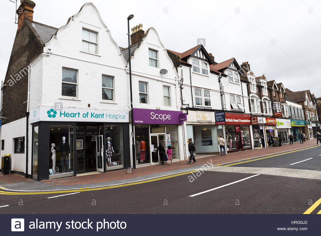 Parade of shops containing cafes and charity shops, Tonbridge High Street, Kent, UK - Stock Image