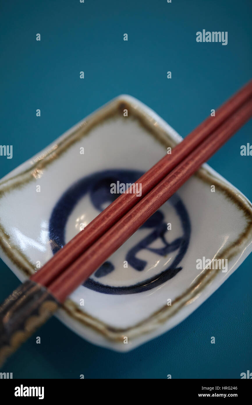 Chinese chop sticks on a small traditional plate, Stock Photo