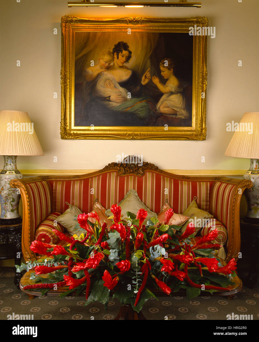 Classic furnishings with a flower arrangement of Crimson trails of furry Amaranthus and bromeliad, mixed with eucalyptus - Stock Image