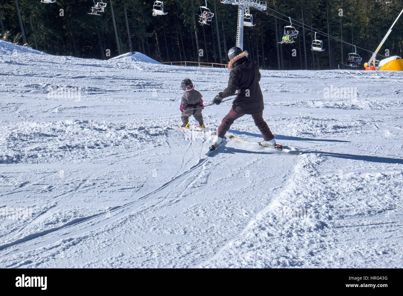 WINTERBERG, GERMANY - FEBRUARY 14, 2017: Mother and child in harness learning how to ski downhill at Ski Carousel - Stock Image
