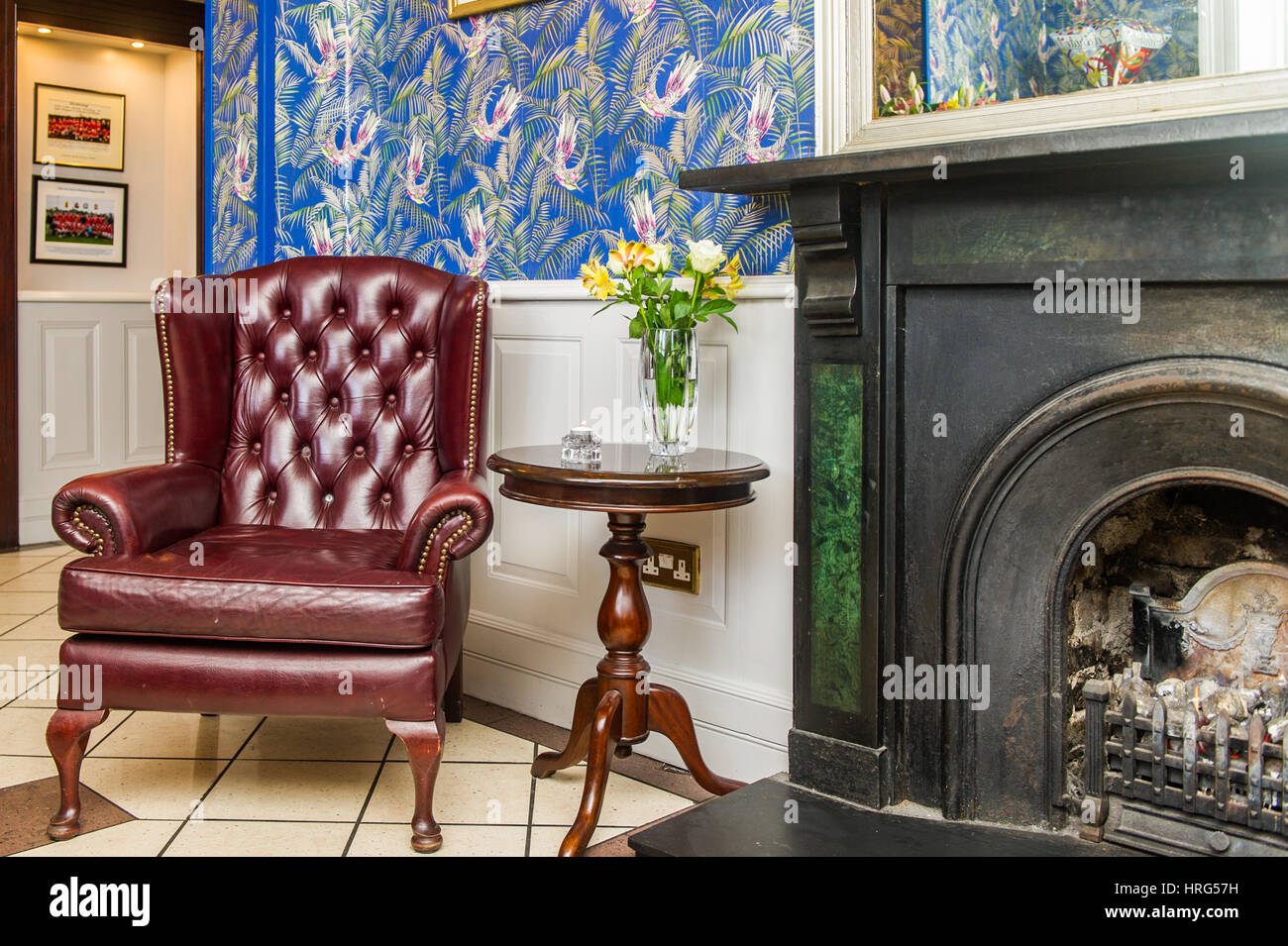 Gentleman's club style armchair next to a fireplace in a hotel reception. - Stock Image