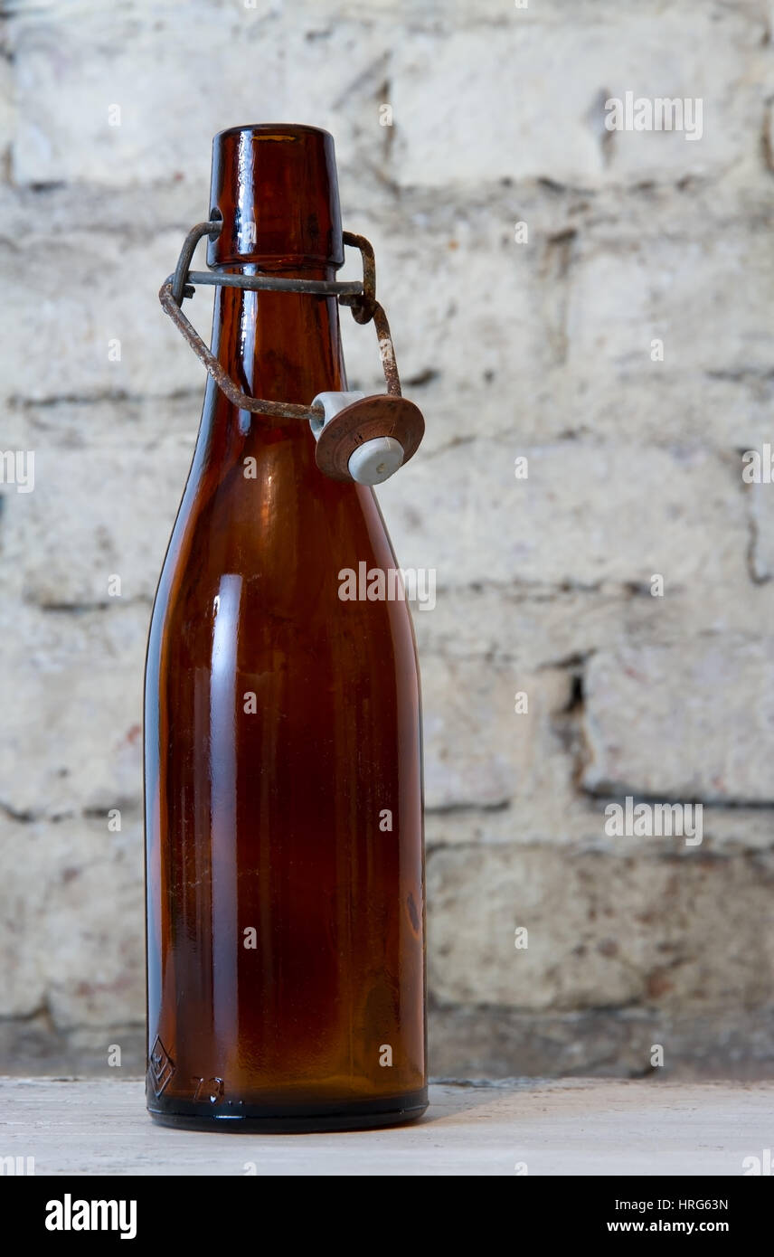 Old Brown Bottle With Stopper And Old Small Glass Standing On