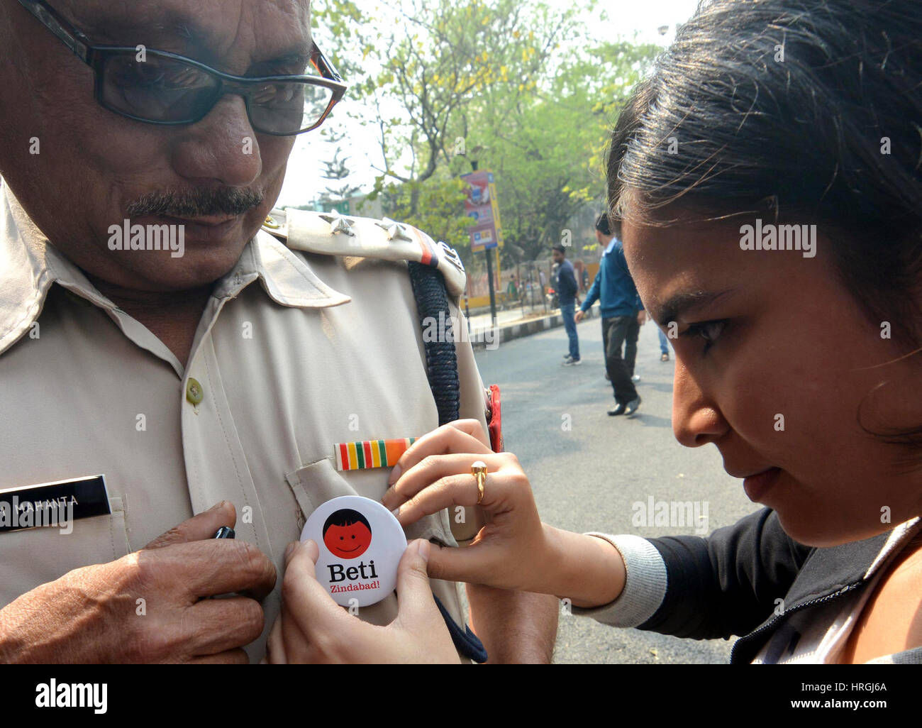 (170303) -- GUWAHATI(INDIA), March 3, 2017 (Xinhua) -- A girl stitches a badge onto shirt of a policeman to promote - Stock Image