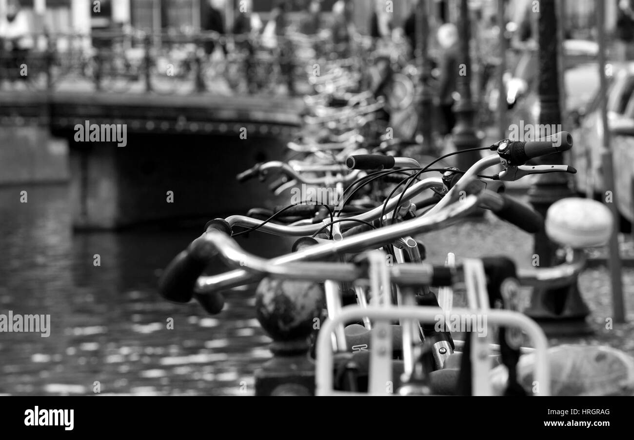 Parked bicycles along a canal in Amsterdam, the Netherlands - Stock Image