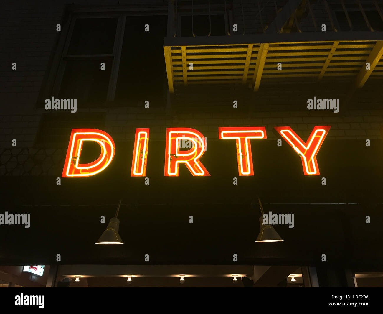 Neon sign at night with the world dirty in red capital letters. - Stock Image