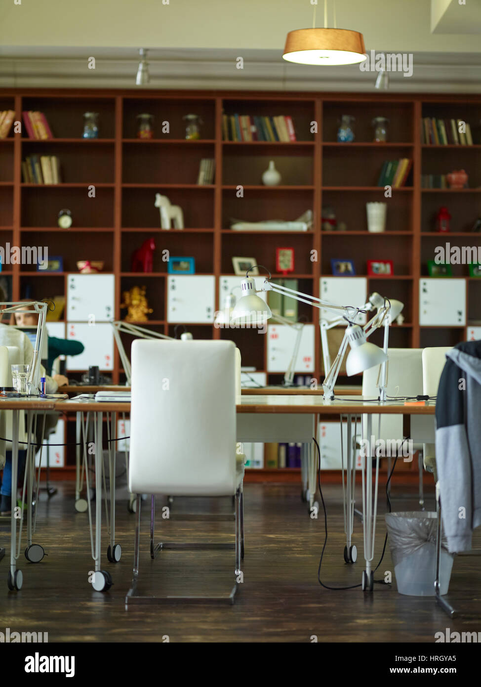 Working desks with lamps against tall bookcases in modern office room with interior in warm brown tones - Stock Image