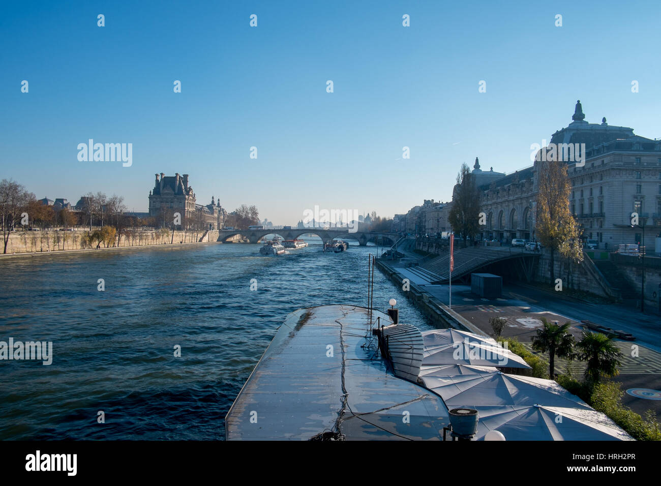 River Seine on a winters day overlooked by the Musée d'Orsay and the Louvre, Le Quai restaurant in foreground, Paris, Stock Photo