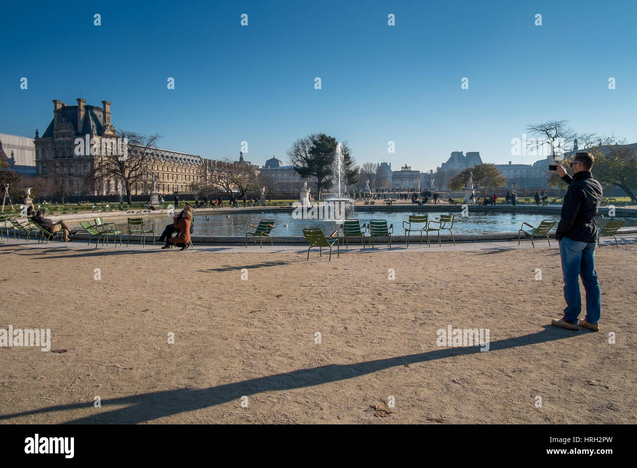 Man taking photograph at the Jardin des Tuileries overlooked by the Louvre museum, Paris, France. - Stock Image