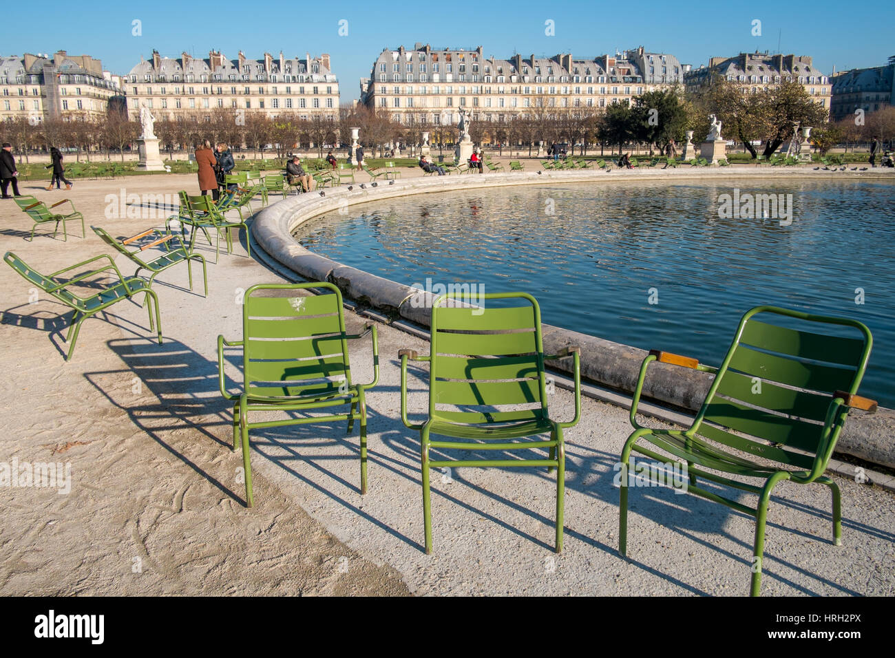 Enjoying the winter sun at Grand bassin octogonal at the Jardin des Tuileries, overlooked by the grand appartments - Stock Image