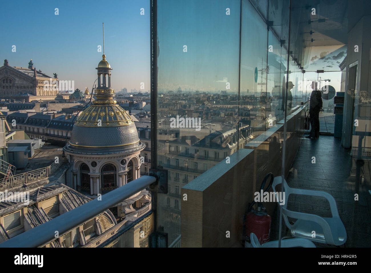 Man viewing the ornate domes of the Galeries Lafayette department store shine in the winter sun with the Palais - Stock Image