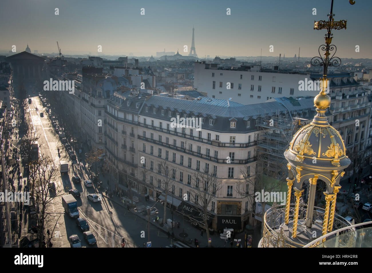 An ornate dome of Printemps department store shines in the winter sun with the Eiffel Tower in the distance. - Stock Image