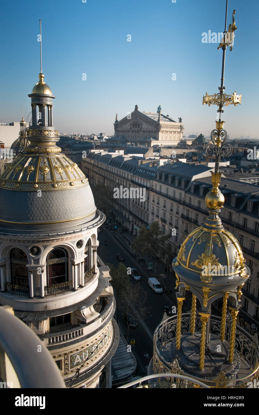 The ornate domes of the Galeries Lafayette department store shine in the winter sun with the Palais Garnier Opera - Stock Image