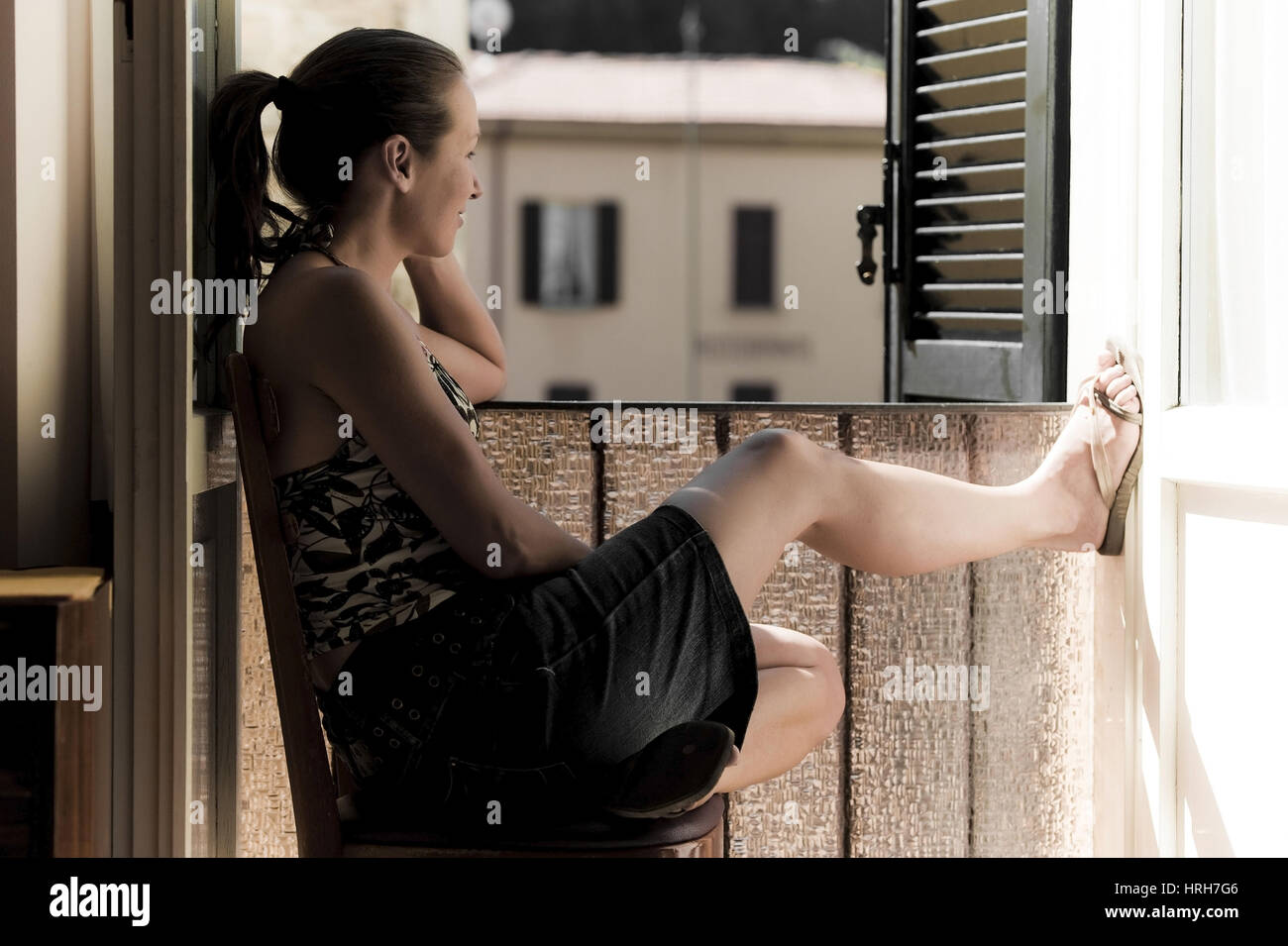 Model released, Junge Frau sitzt am Fenster - woman sitting front of a window Stock Photo