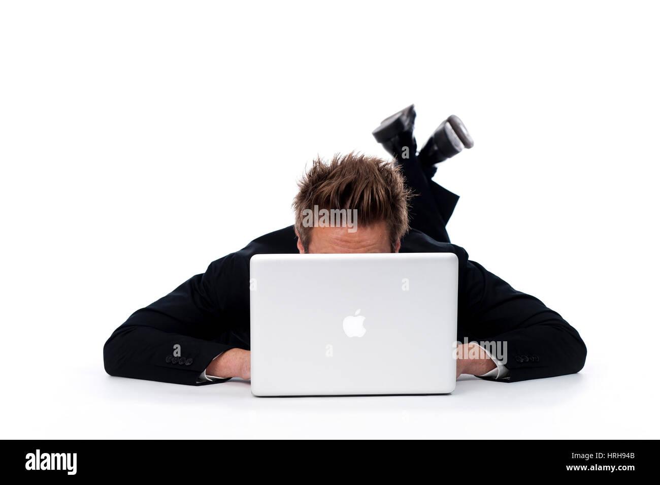 Model released, Geschaeftsmann liegt versteckt hinter Laptop am Boden - businessman behind a laptop - Stock Image