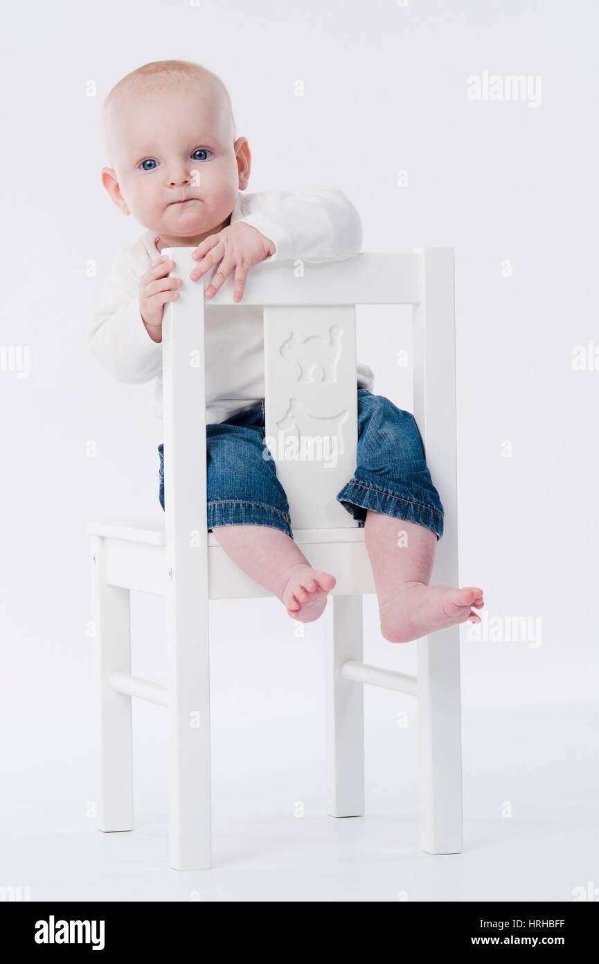 Model released, Baby auf Kinderstuhl - baby on chair - Stock Image
