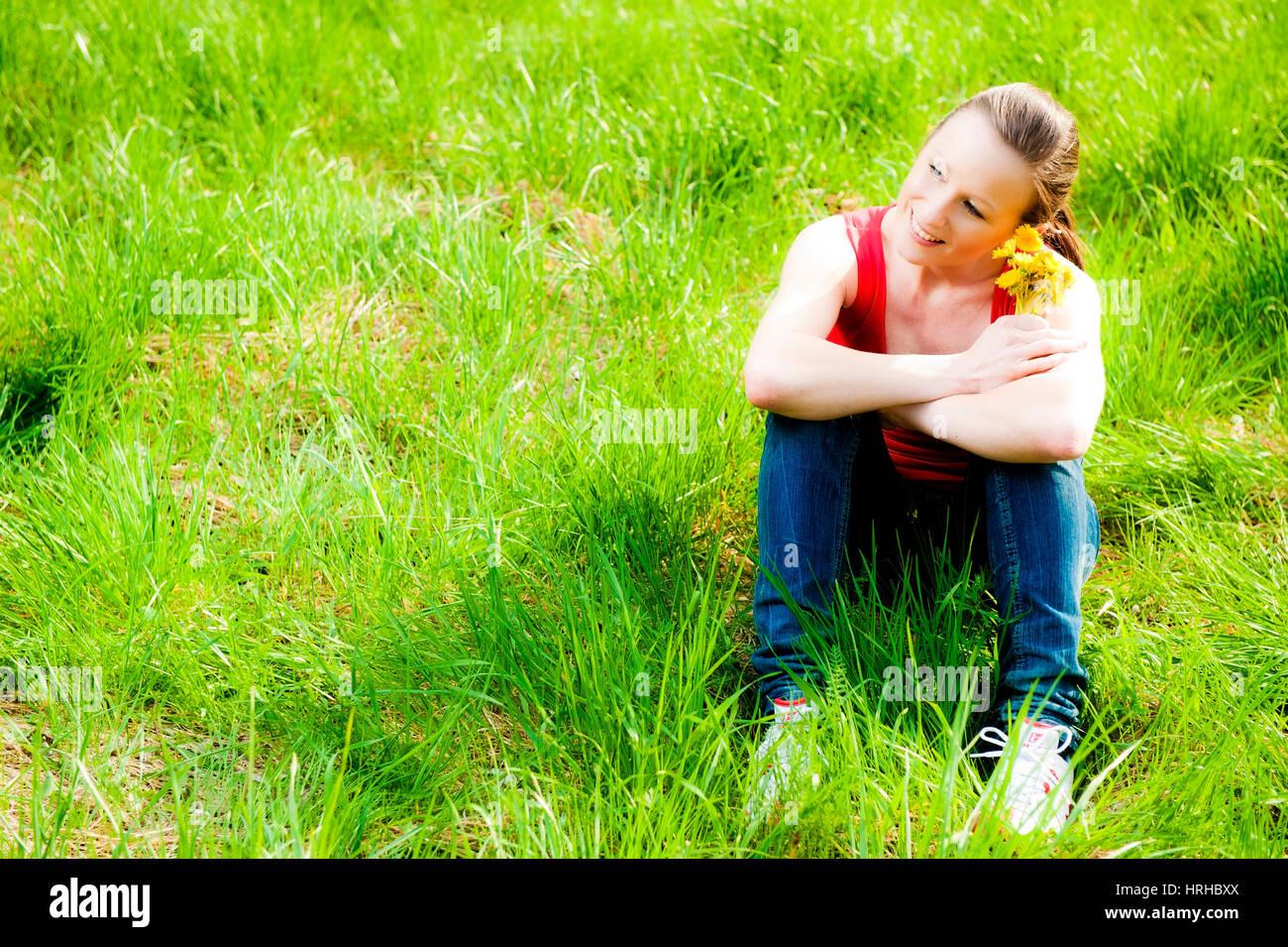 Model released, Junge Frau mit Loewenzahnblumen in Fruehlingswiese - young woman in spring Stock Photo