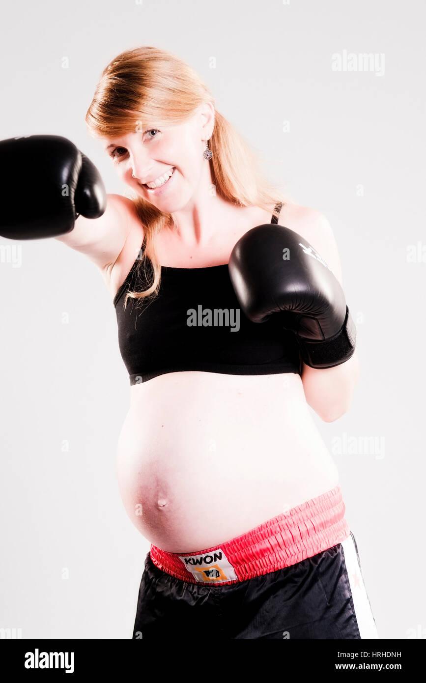 Schwangere Frau mit Boxhandschuhen - pregnant woman boxing - Stock Image