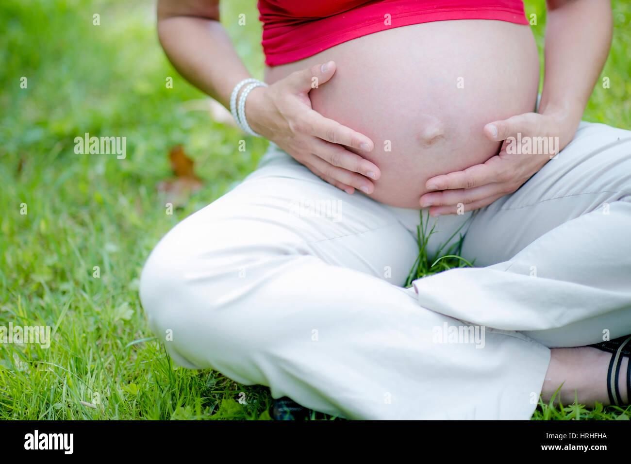 Schwangere Frau greift sich an den Babybauch - pregnant woman Stock Photo