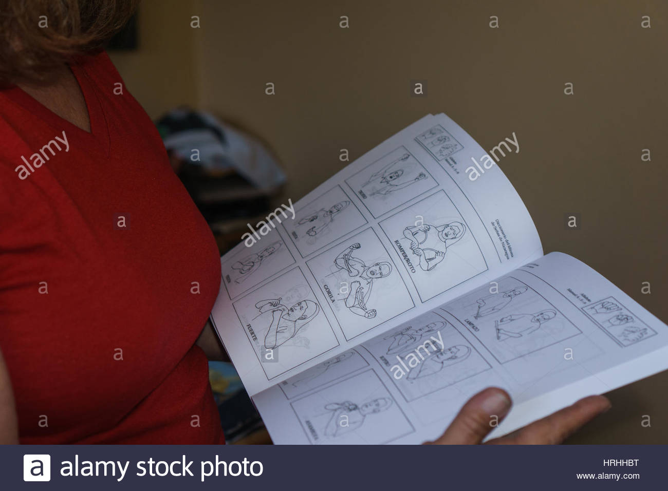 NGO employee looking at dictionary of Nicaraguan Sign Language - Stock Image