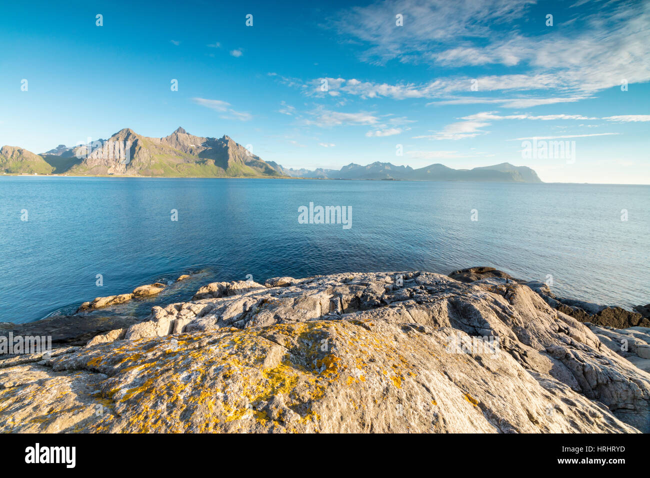 Sun shines on the blue sea and the rocky peaks at night during summer, Vikten, Nord Trondelag, Lofoten, Norway, Stock Photo