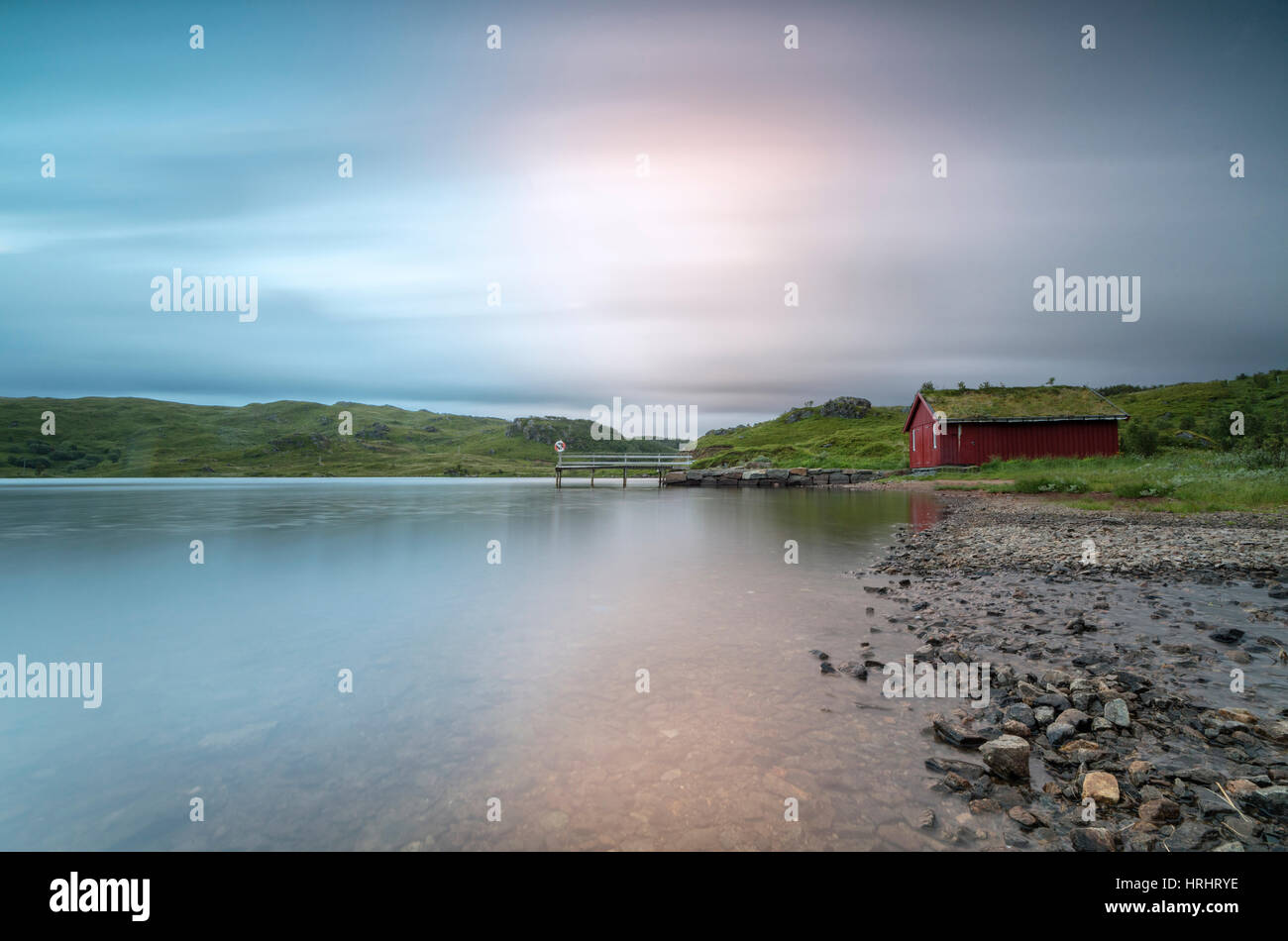 Pink lights of the midnight sun illuminate sea and the typical rorbu, Holdalsvatnet, Vestvagoy, Lofoten Islands, Stock Photo