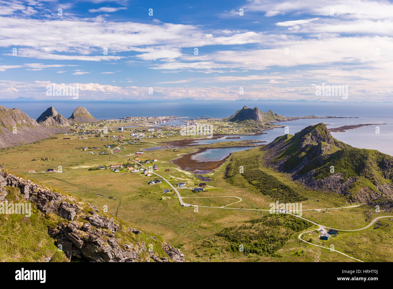 View of village of Sorland framed by green meadows and sea, Vaeroy Island, Nordland county, Lofoten archipelago, - Stock Image