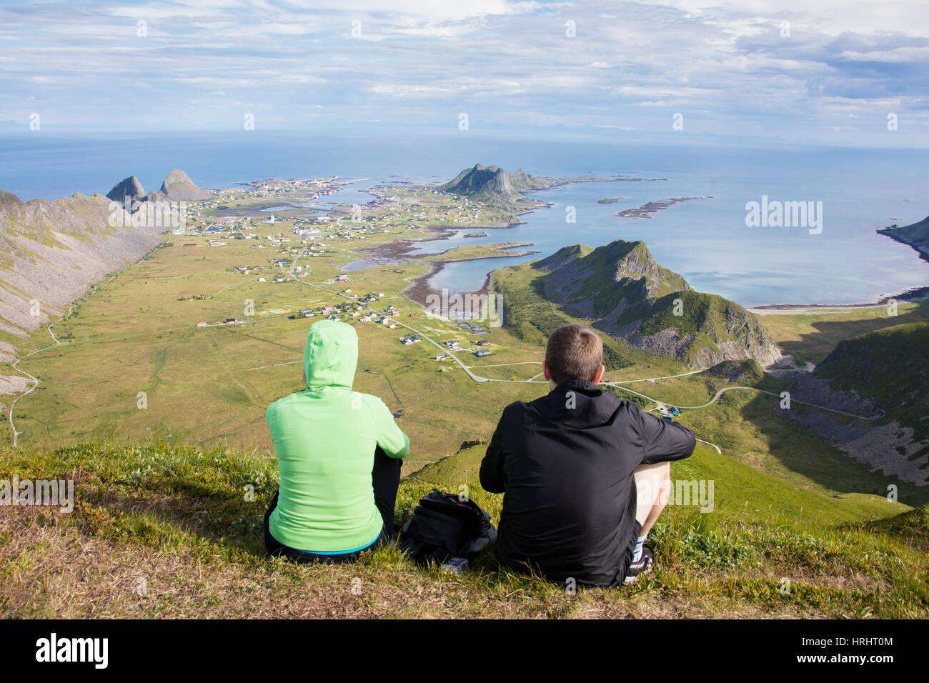 Couple on top of peak admire sea framing the village of Sorland, Vaeroy Island, Nordland county, Lofoten archipelago, - Stock Image