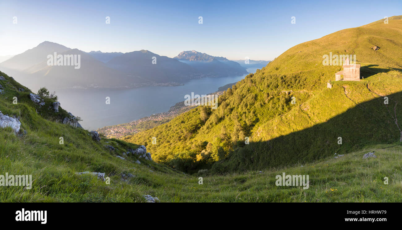 Sun on Church of San Bernardo lights up the landscape around the blue water of Lake Como at dawn, Musso, Lombardy, - Stock Image
