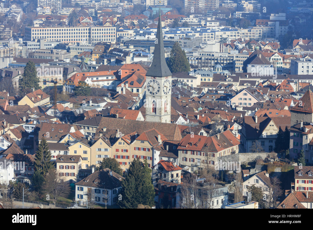 View of bell tower of Church of St. Martin and the city of Chur, district of Plessur, Canton of Graubunden, Switzerland - Stock Image