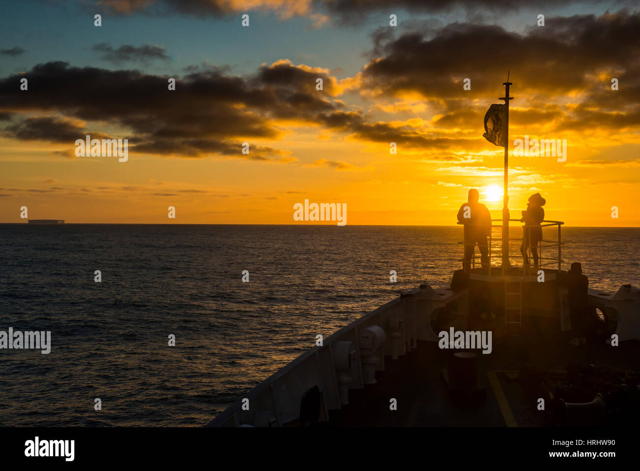 Tourists standing on the bow of a cruise ship watching the sunset, South Orkney Islands, Antarctica, Polar Regions - Stock Image