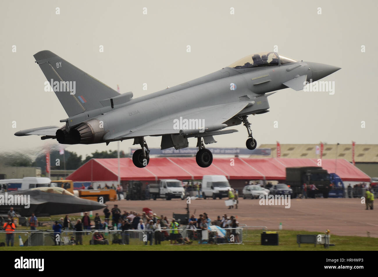 RAF Typhoon FGR4 fighter plane landing at the Royal International Air Tattoo, Fairford with crowd. Space for copy - Stock Image