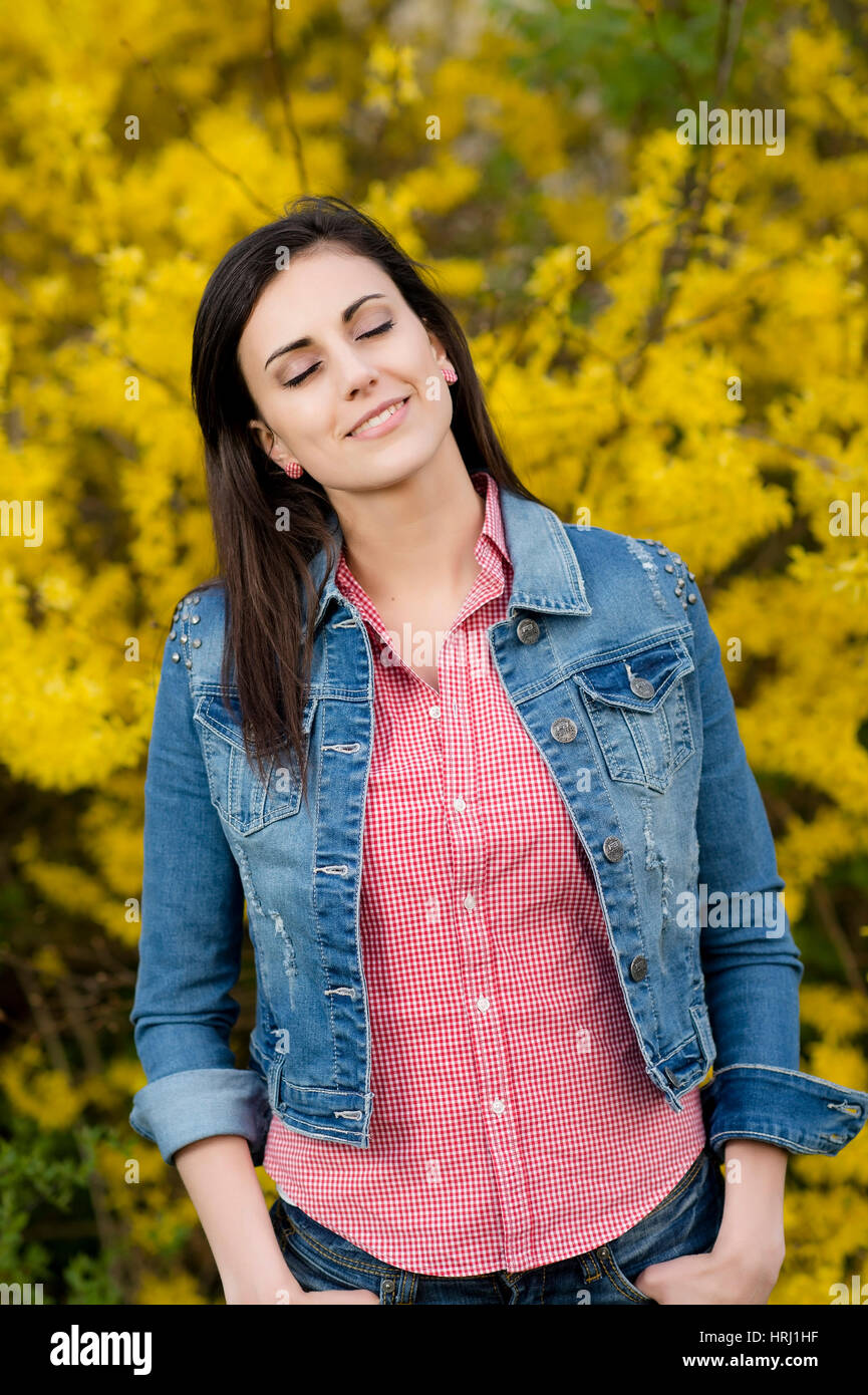 Junge Frau vor Forsythienstrauch - woman front of forsythia - Stock Image