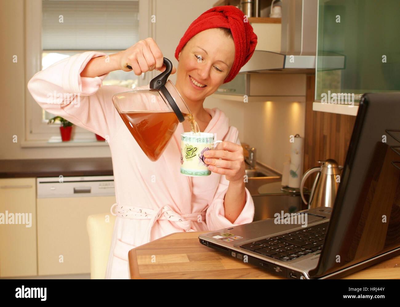 Junge Frau im Morgenmantel arbeitet am Notebook an der Bar und schenkt sich Tee ein - woman in bathrobe using laptop - Stock Image