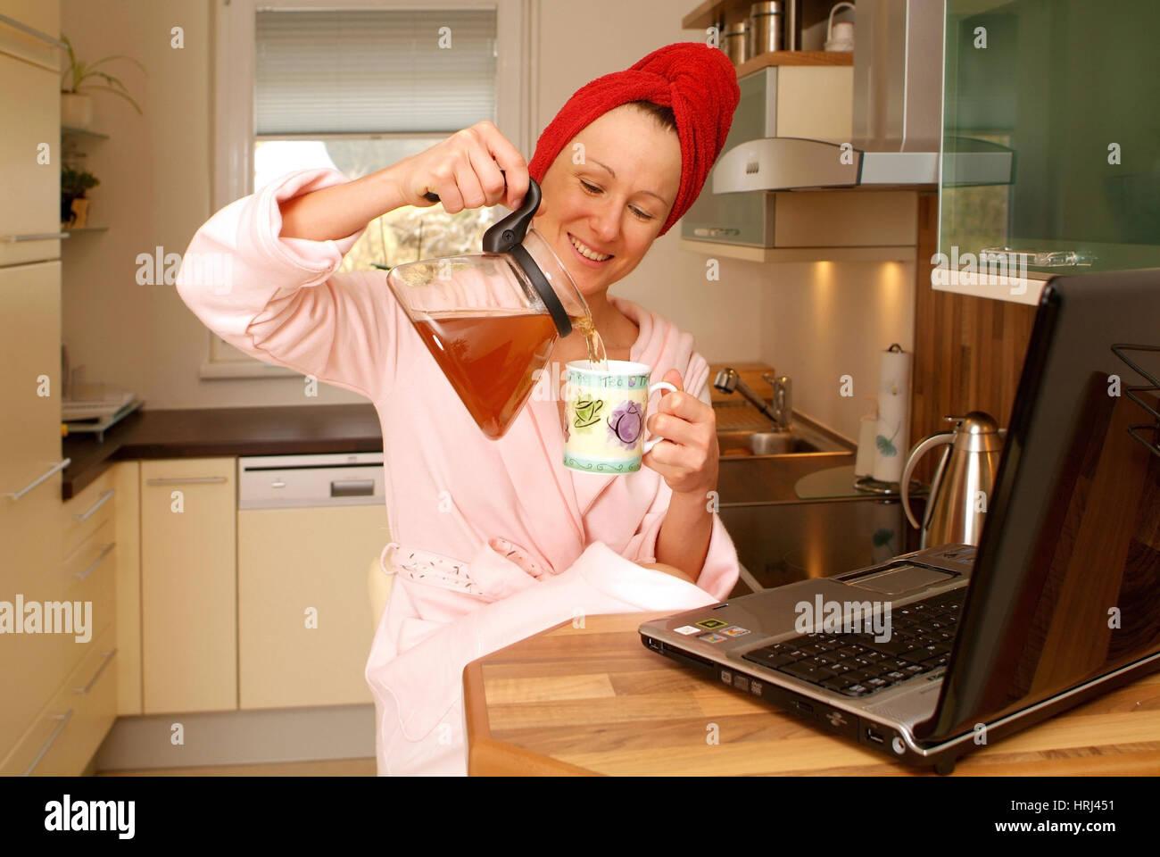 Junge Frau im Morgenmantel arbeitet am Notebook an der K?chenbar und schenkt sich Tee ein - woman in bathrobe using - Stock Image