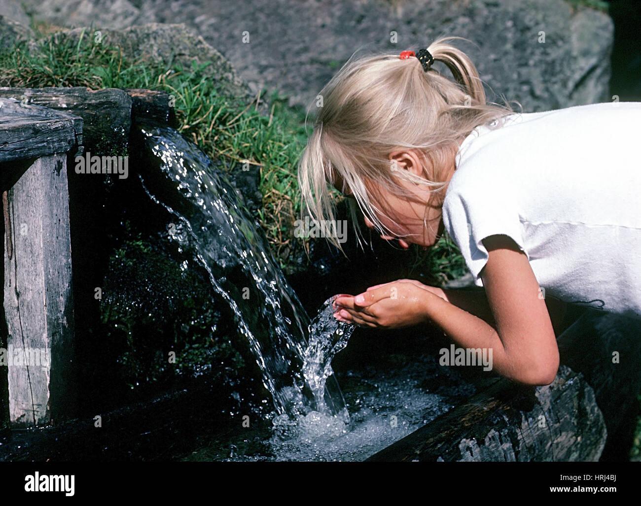 M?dchen trinkt Brunnenwasser - girl drinking well water Stock Photo