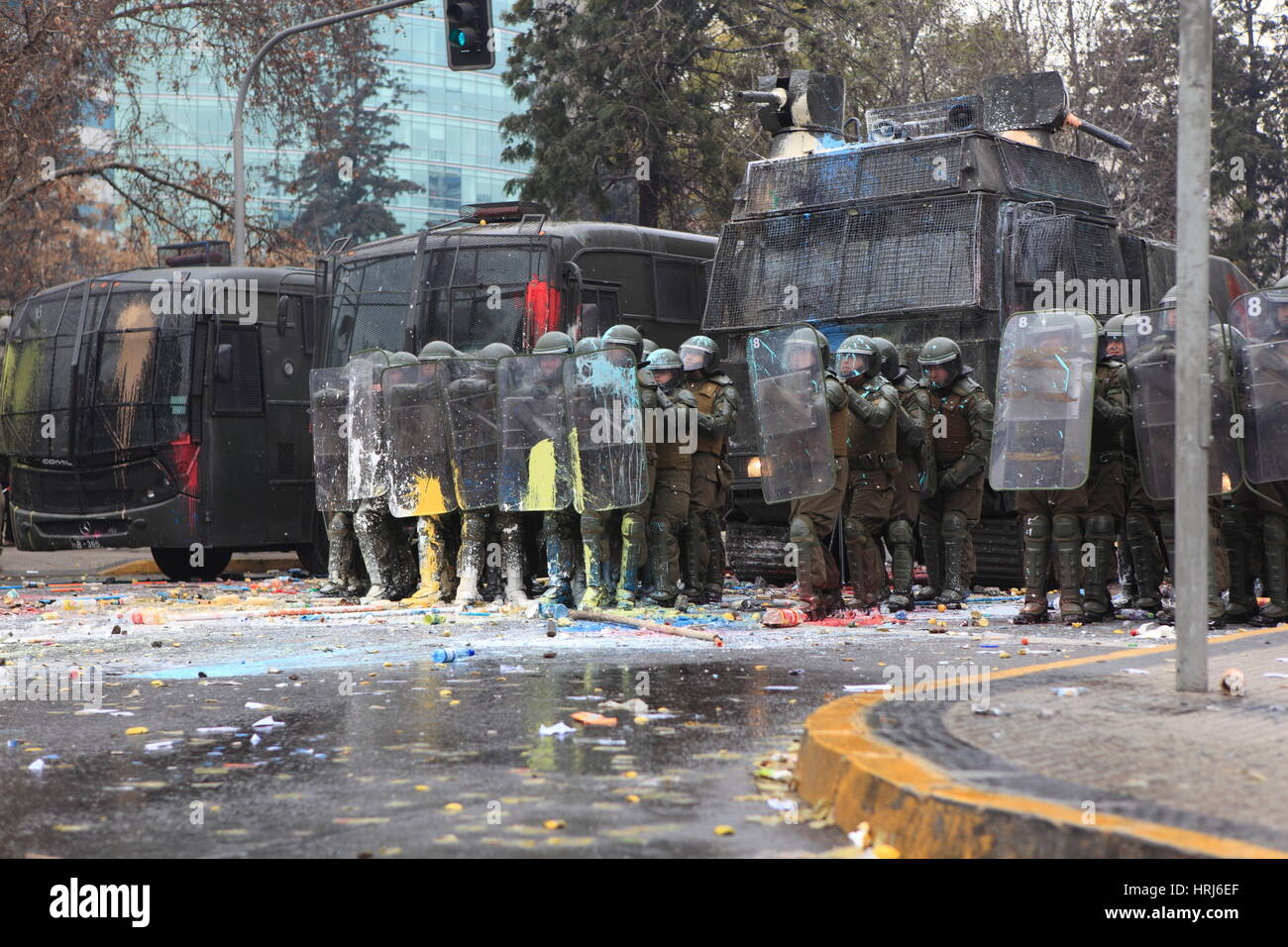 A line of Chilean riot police observing protesters who threw bottles with paint, during a demonstration in Santiagos - Stock Image