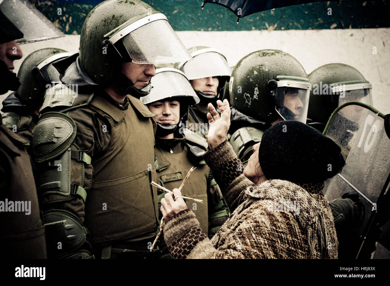 Old woman chides Chilean riot police (carabinero) during a student strike in Santiago, Chile. - Stock Image