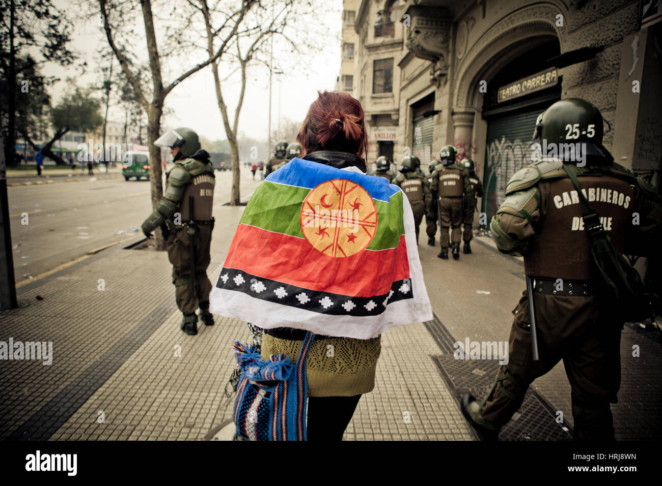 A woman demostrator with a Mapuche flag on his back walks by riot police during a student strike in Santiago, Chile. Stock Photo
