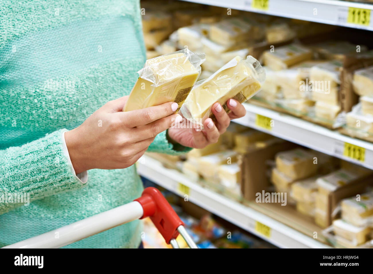 Buyer chooses the cheese in the store on the background of shelves with products - Stock Image