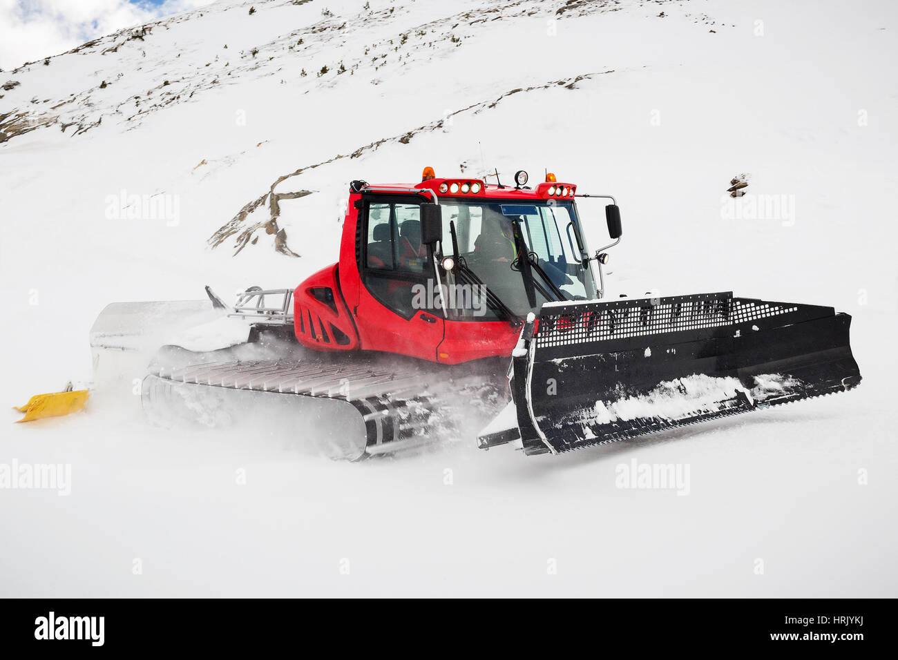 A snow plough grooming the piste at Obergurgl in Austria. Motion blur on the fast moving caterpillar tracks. - Stock Image