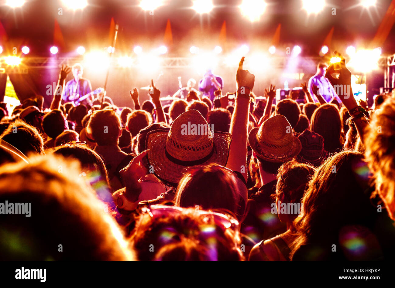 Crowd enjoying a rock band's performance at a music festival - Stock Image