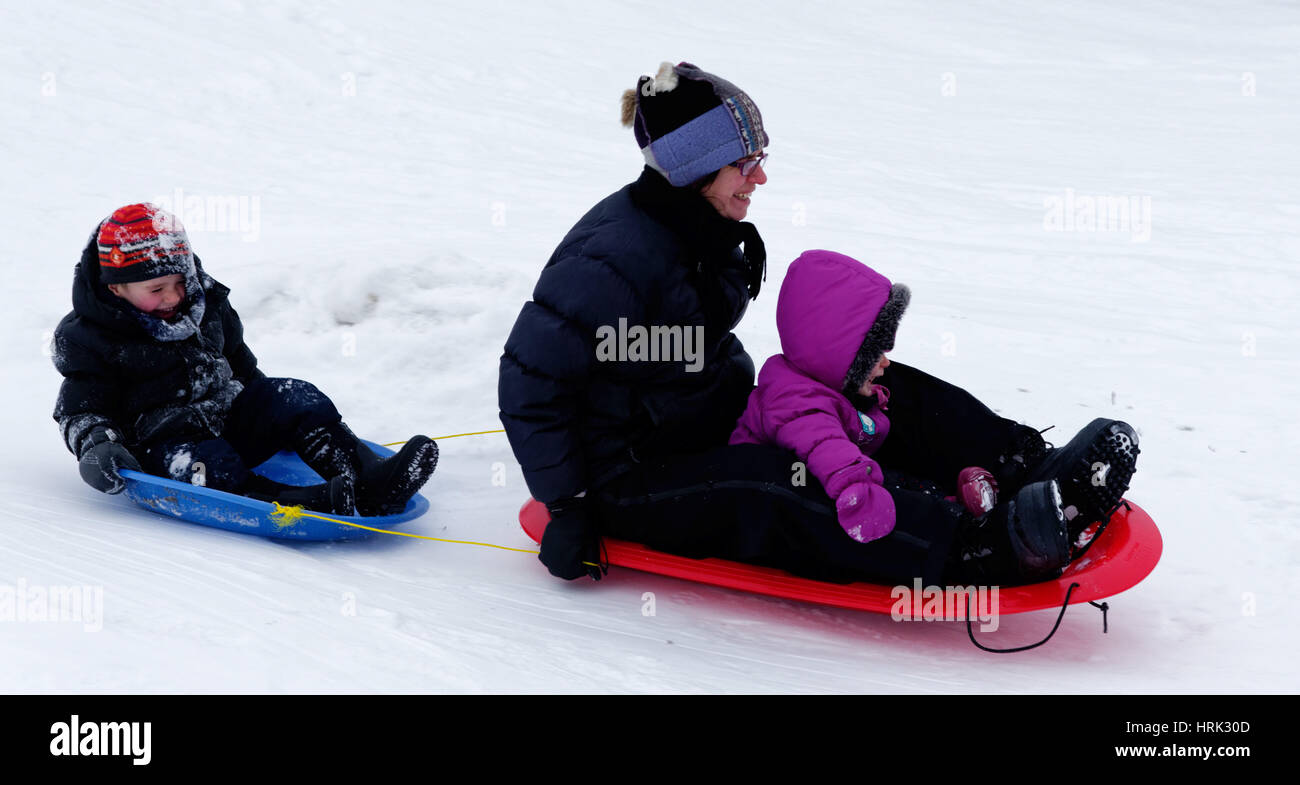 A laughing mum with her son and daughter sledging - Stock Image